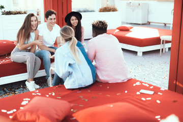 Laughing women telling with cheerful men while relaxing on comfortable couch outside