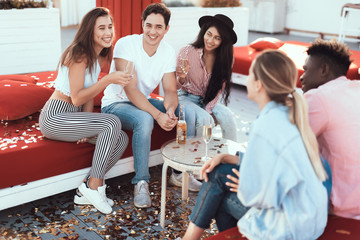 Satisfied girls speaking with cheerful males while sitting on comfortable couch. They tasting alcohol beverage