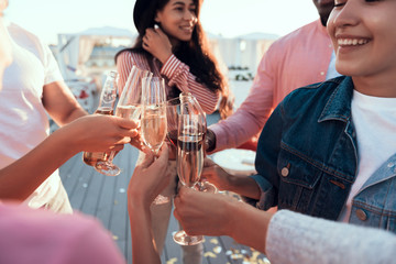 Outgoing women and cheerful males tasting delicious champagne while speaking together during party
