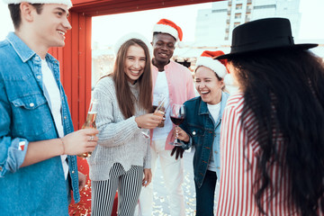 Positive ladies and beaming males speaking during new year party. They wearing red hats