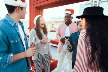 Laughing women and cheerful men talking together while having fun during christmas celebration