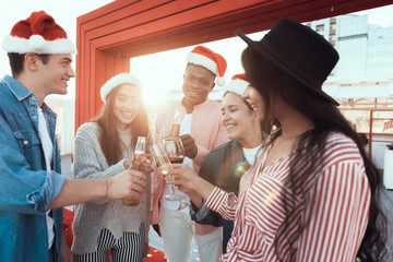 Positive males and cheerful ladies speaking while tasting alcohol liquid. They celebrating new year while wearing red hats