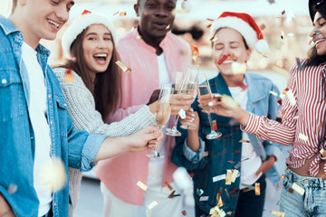 Happy females and cheerful males talking while having fun during christmas. They throwing confetti
