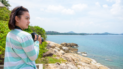 Young woman was happy to photography with dslr camera on the rock near the sea under the summer sky at Koh Samui island, Surat Thani province, Thailand