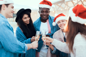 Smiling males and beaming girls tasting alcohol liquid during conversation. They having fun during party