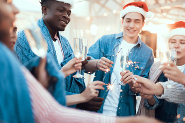 Pleased men and smiling girls keeping bright firework sparklers in hands while drinking appetizing glasses of champagne