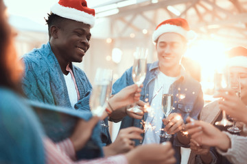 Satisfied guy celebrating christmas with cheerful male and female comrades. They holding bengal lights in arms and tasting delicious champagne