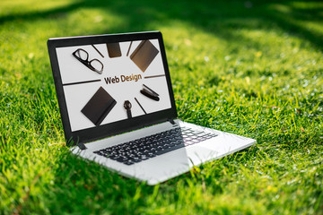 Laptop with advertising screen on the background green grass, outdoor office. Design concept. Business idea.