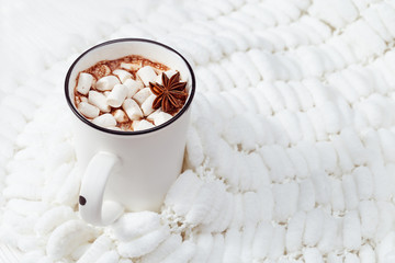 Hot milk cacao with marshmallow on fluffy white cloth background. Hot sweet beverage.