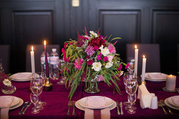 Elegant magenta color velvet table cloth on beautiful wedding table with dishes, candles and flowers. Restaurant. Wedding decoration concept