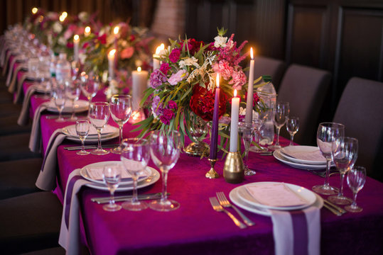 Elegant dark pink wedding banquet table with glasses, dishes and flowers decoration indoors in restaurant. Gorgeous long wedding table. Wedding decoration concept. Magenta color
