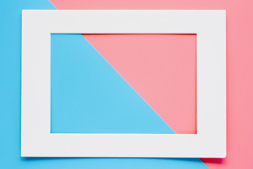 White paper frame on pink-blue pastel color background. Flat lay and top view image.
