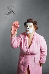 femme ronde avec peignoir et bigoudis chassant un moustique dessiné