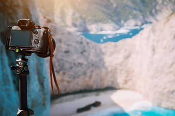 Digital photo camera on tripod focused on Shipwreck in Navagio beach in morning sun light. Famous visiting landmark location on Zakynthos island, Greece