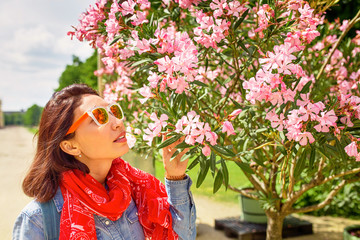 Woman sniffing nerium oleander flowers in the garden