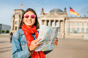 Beautiful young woman looking at map guide while standing in front of Bundestag building at sunset in Berlin. Travel in Germany concept