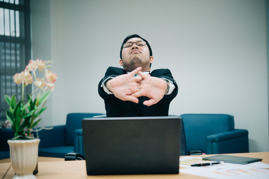 Asian officer man stretching body at the desk of office from back angle,Thailand people,Businessman tired from hard work