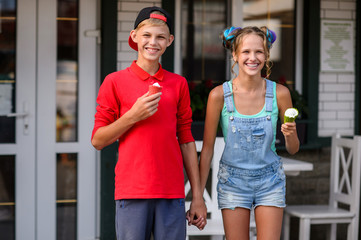 Young couple eating ice cream. Attractive friends at cafe. Romantic love moment of teenagers