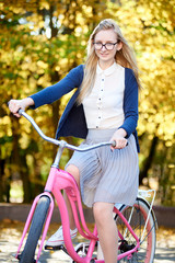 Portrait of blond long-haired attractive traveler girl in glasses, skirt and blouse posing on modern pink lady bicycle on lit by autumn sun park on bright colorful golden bokeh trees background.