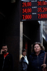 People walk past an electronic board, which shows currency exchange rates, in Buenos Aires' financial district