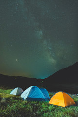 Camping under the starry sky with Milky Way above the horizon
