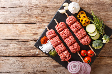 Homemade kebabs from raw minced meat on skewers with spices, herbs and vegetables close-up. horizontal top view