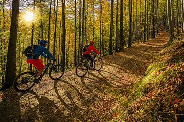 Cycling, mountain biker couple on cycle trail in autumn forest. Mountain biking in autumn landscape forest. Man and woman cycling MTB flow uphill trail. Wall mural