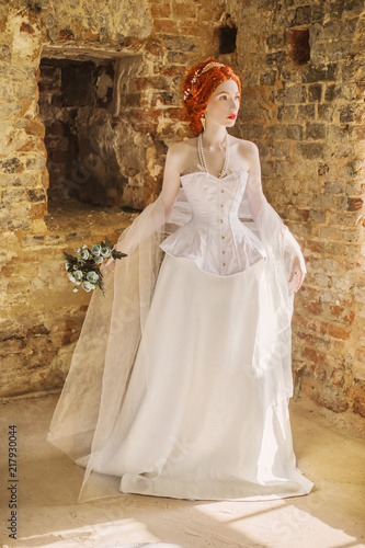 2b554a0ee5b Doll in corset. Renaissance princess in palace. Fairytale queen in white  dress against backdrop of old stone wall.