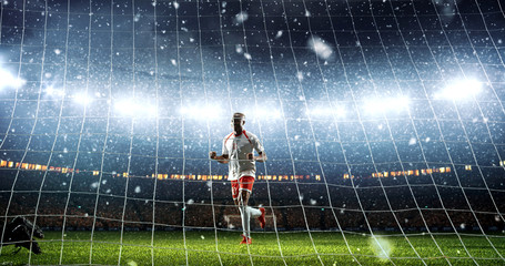 Attacker scores a goal and celebrates victory on a professional soccer stadium while it`s snowing.