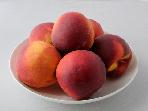 Still life of peaches. A few fresh peaches on a white plate.