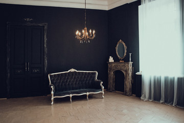 Black room in the castle with a window, a chandelier, a sofa and mirror and fireplace. Space where you can put a person. Wall mural