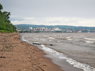 Park Point Beach on Lake Superior with Duluth, Minnesota under cloudy skies