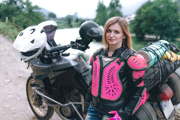 close up portrait girl in pink body armor with big adventure motorcycle with bags and camping equipment, off road travel jorney, traveling together, mountains dirt road and river
