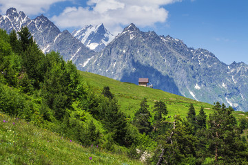 Alpine landscape of green meadow and rocky mountains in a clear sunny summer day. Amazing rural mountain scene hills in Alps with lonely house on hillside. Springtime in beautiful nature.
