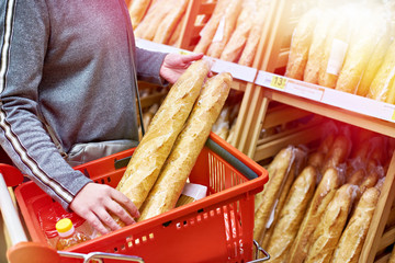 Buyer with baguettes in basket at store