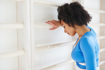 Side view of black woman in sportswear leaning on wooden gymnastic wall bars looking upset and tired