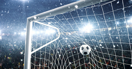 Photo of the ball that flies into a goal on a professional soccer stadium while it's snowing
