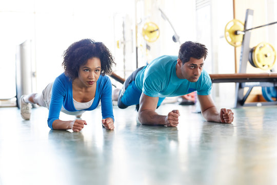 Diverse man and woman working out together and standing in plank position training abdomen together in gym
