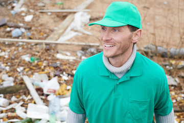 Cheerful adult volunteer in green uniform standing at polluted place and looking away