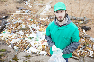Young volunteer in green uniform standing at pile of litter and looking at camera with confidence