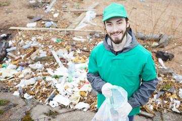Smiling bearded volunteer in green uniform holding bag for litter and looking at camera