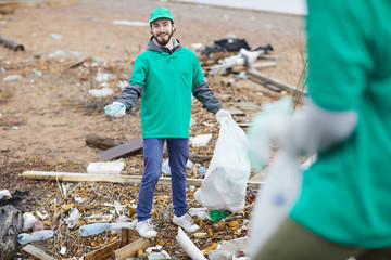 Cheerful young volunteer in green uniform standing with garbage bag while cleaning place from garbage