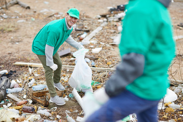Cheerful activists in green uniform collecting garbage on polluted place