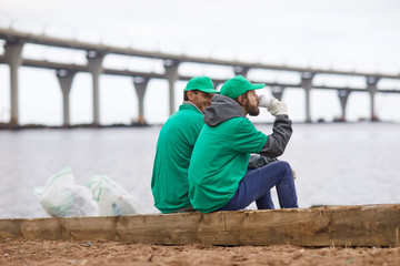 Side view of volunteers in green uniform sitting with coffee cups and relaxing on shore