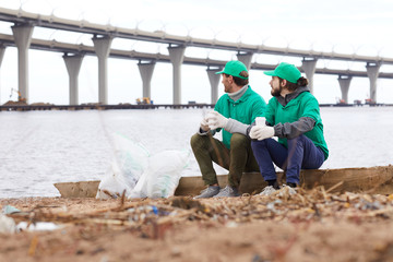 Volunteers in green uniform sitting with paper cups and looking away while resting on shore