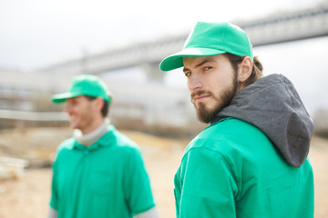 Side view of volunteer in green uniform standing and looking at camera