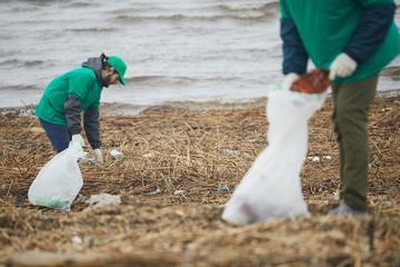 Two volunteers in green uniform working and cleaning shore from garbage