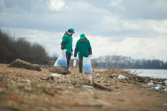 Two volunteers standing and collecting rubbish to bags on shore