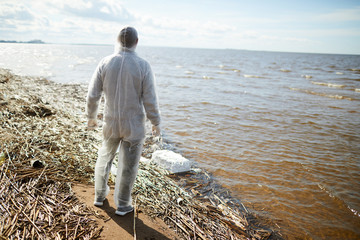 Back view of volunteer in white protective suit standing on polluted shore