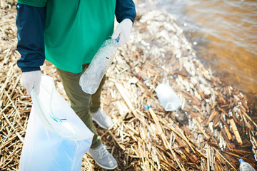 Crop unrecognizable activist in green uniform putting garbage to plastic bag on shore